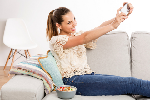 Young woman taking selfie on couch with food