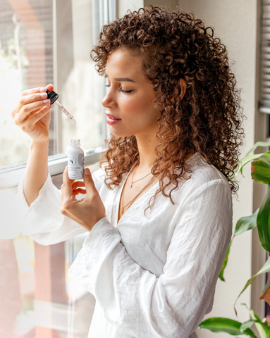 Young woman in robe smelling essential oils