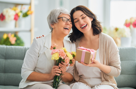 mother and daughter celebrating mothers day with gifts and flowers