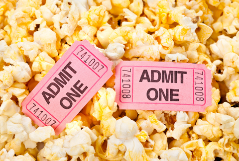 two pink movie tickets in popcorn