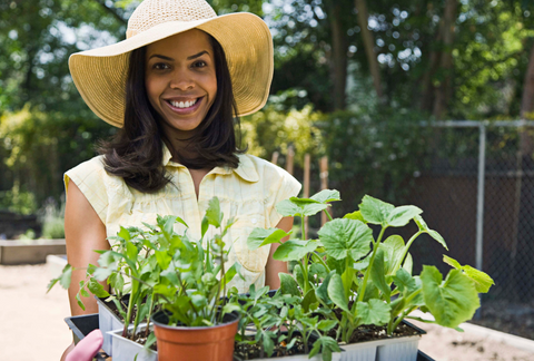happy woman holding plants for gardening