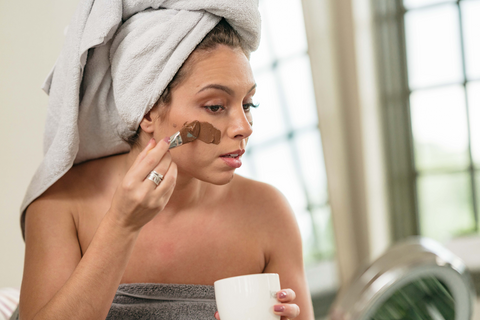 young woman applying coffee face mask