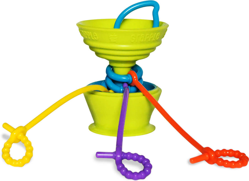 The Grapple® toy tether is a green, apple-shaped adjustable toy holder that suctions to any smooth surface and holds your baby's favorite toys with colorful silicone straps.