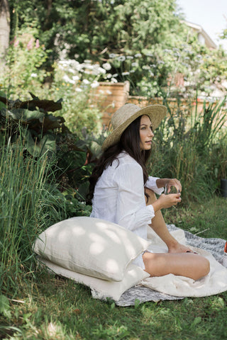Model sits and enjoys a picnic in an English garden surrounded by ANARA pillows and blankets