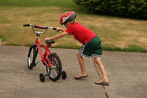 kid with training wheels on his bike