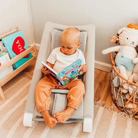 Boy reading in his play corner in the Bamboo 3DKnit Bouncer