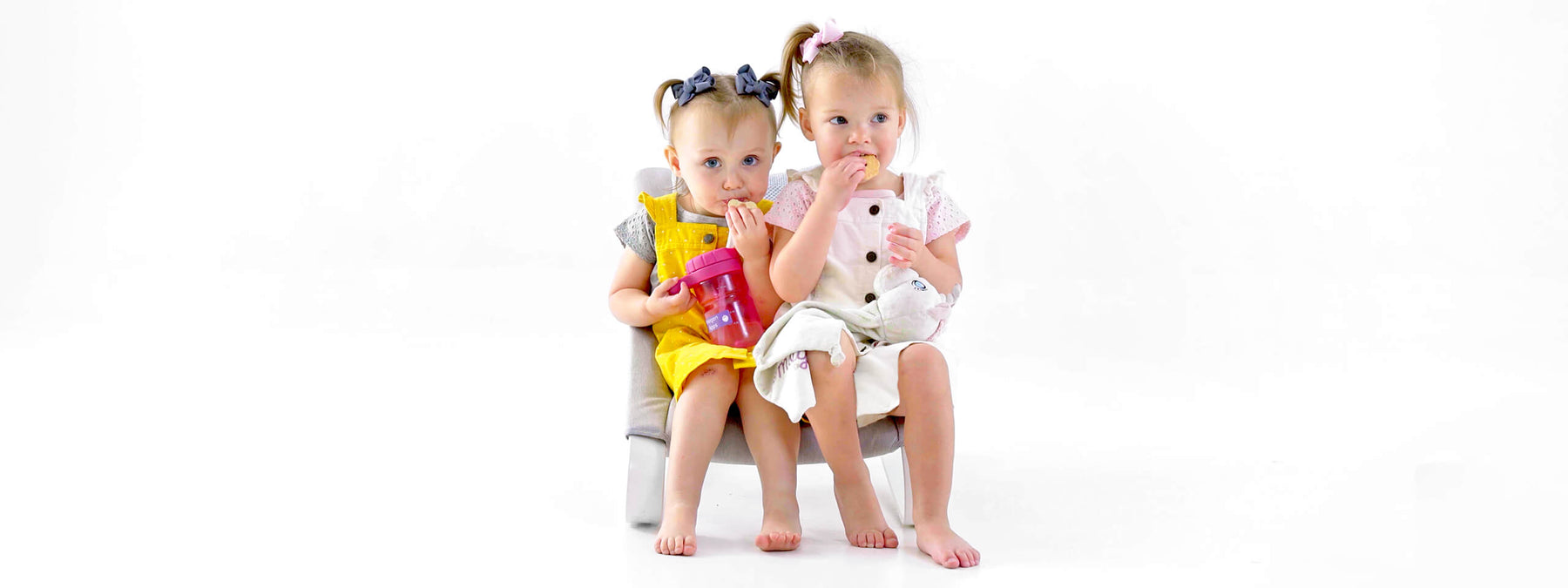 Baby rocker seat with two little girls eating cookies
