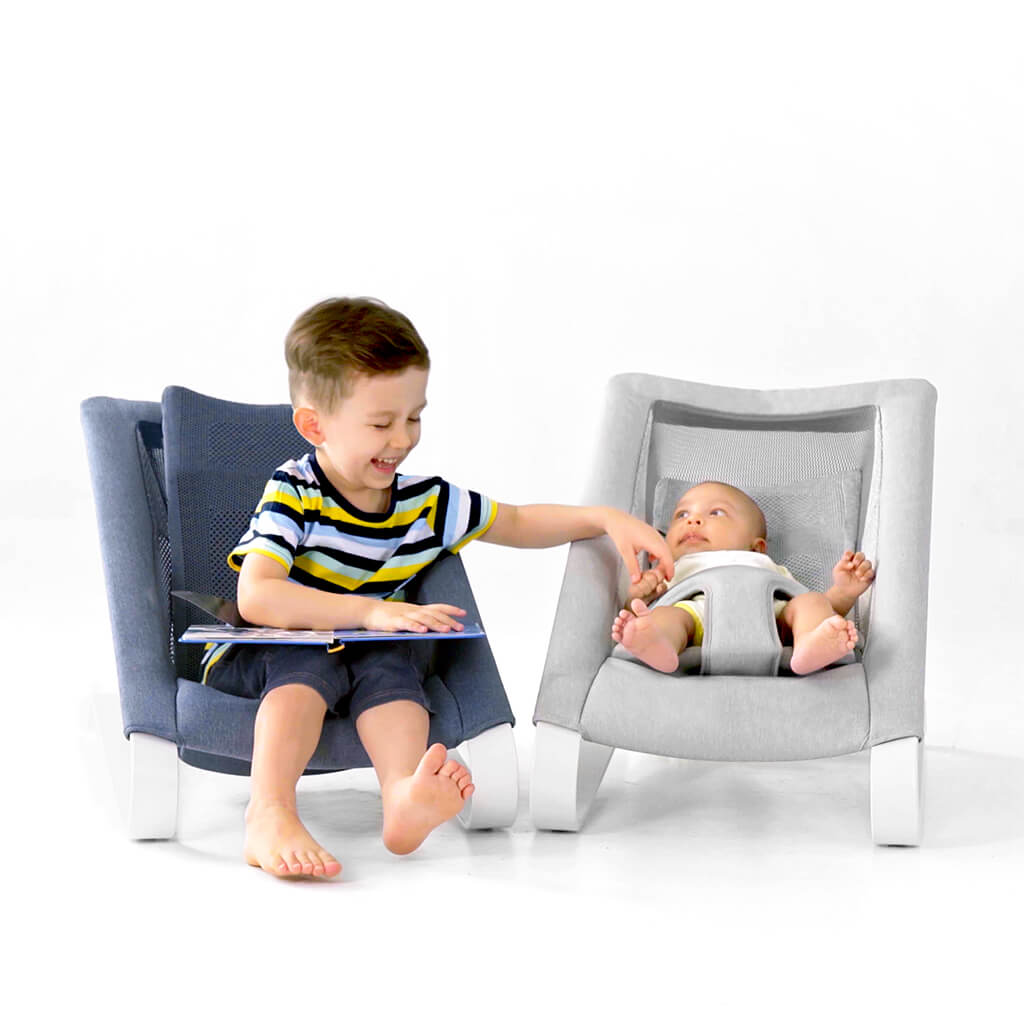 Toddler reading a story to a newborn baby on their infant rocker chair