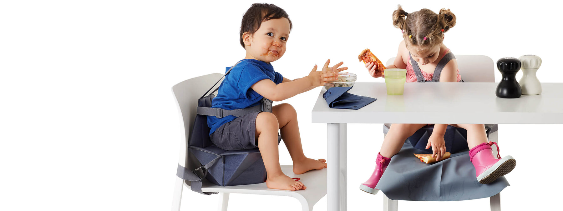 Two little kids eating at a table seating on their pop-up baby booster seat