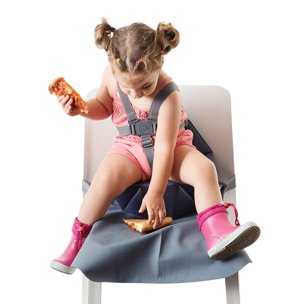 little girl eating pizza on her grey booster seat with a seat cover