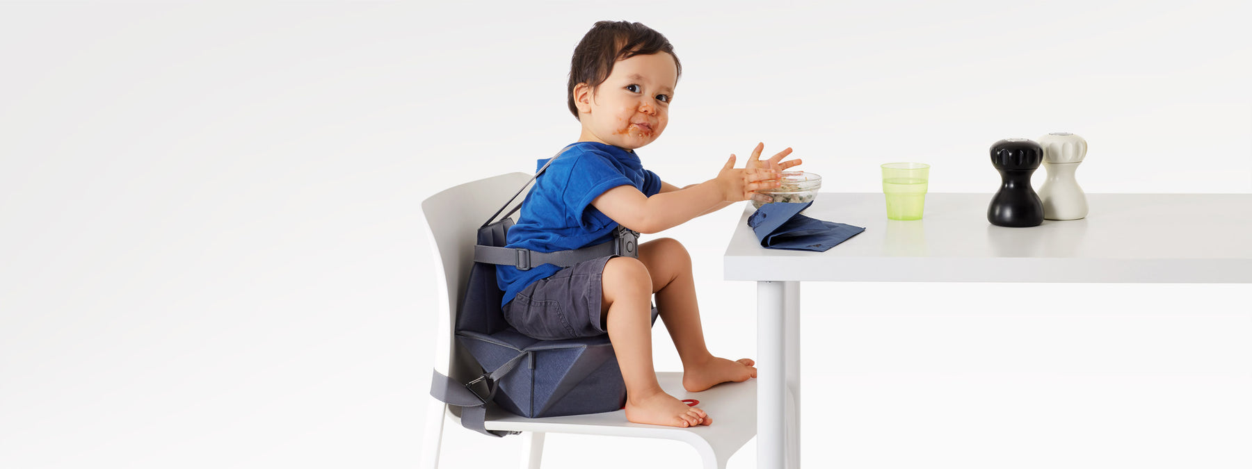 Baby boy seating on a compact high chair eating bolognese