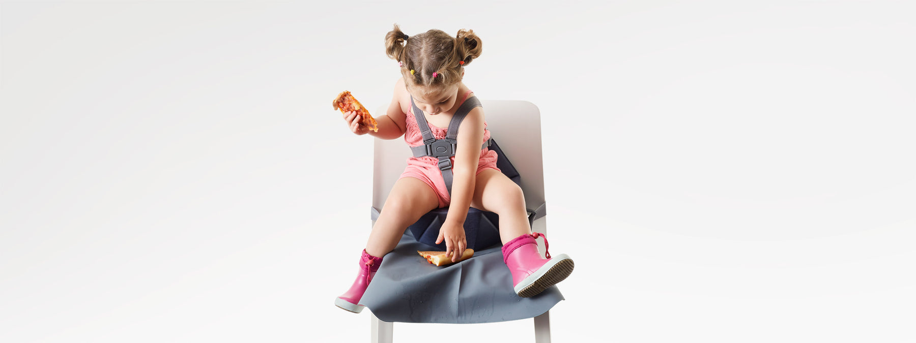 little girl on a baby booster seat with a seat cover eating pizza