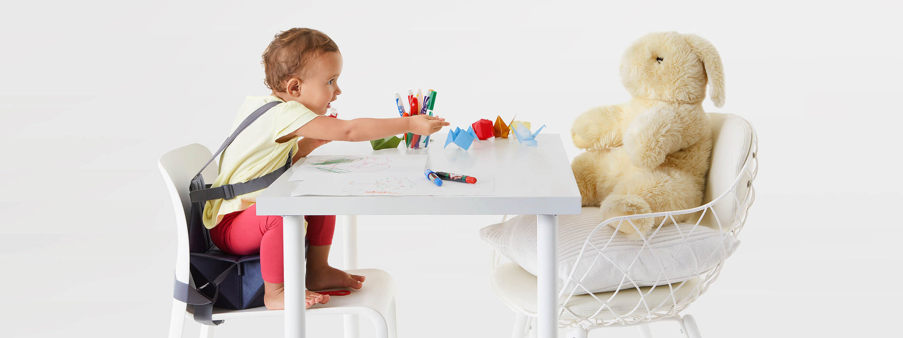Pop-up™ Booster Baby Seat with little kid seating on it