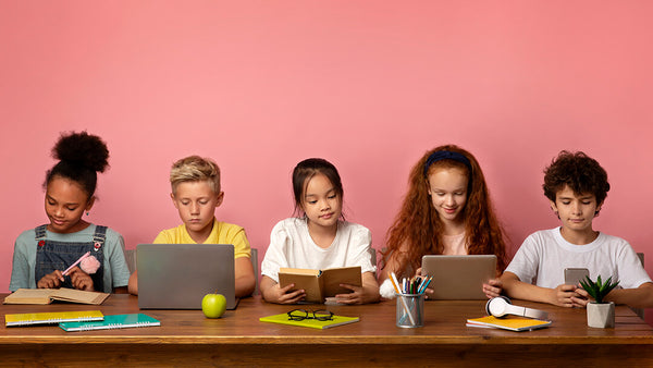 Children at table with their books and devices