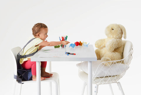 Little girl sitting at the table with coloring activity and a toy bunny.