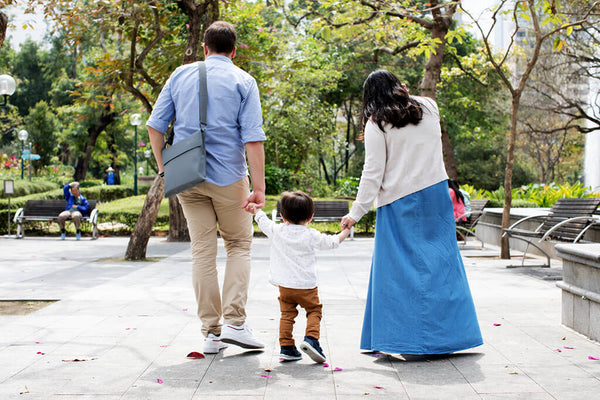 Parents holding baby's hand walking in the park with foldable booster on father's shoulder.