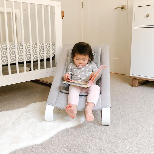 Little Girl in a Bamboo 3DKnit Bouncer is reading