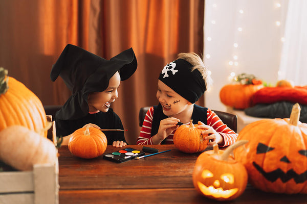 Two kids in costume carving pumpkins