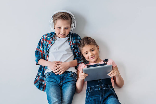 Two happy kids with headphone and device