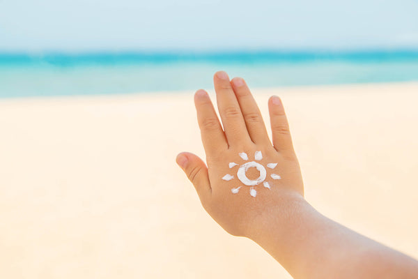 Child's hand with sun screen at the beach