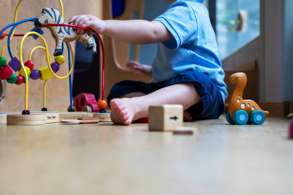 Boy plays with toys on the floor
