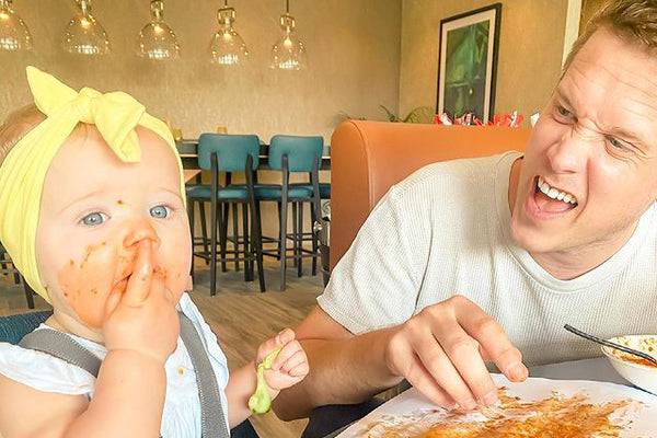 Father at table with messy daughter
