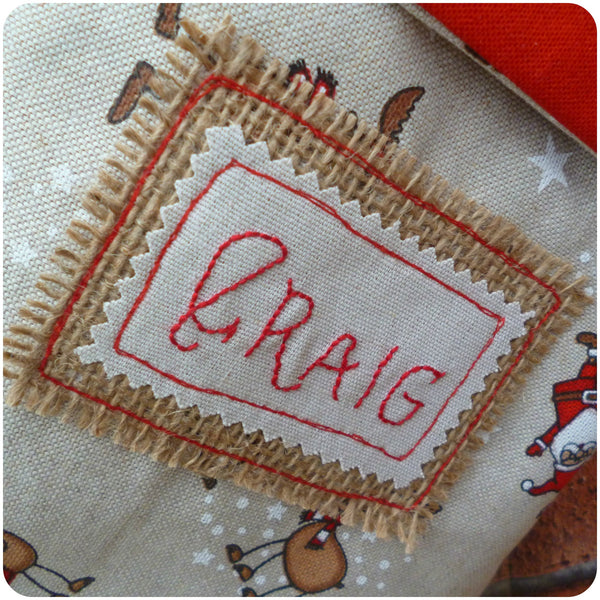 Personalised Santa Stocking, embroidered name patch close up on hessian
