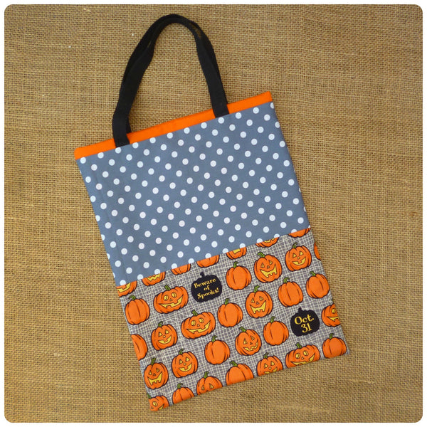 Personalised Pumpkin Treat Bag Flat Lay, Grey Pumpkin fabric, Grey polka dot, black handles, orange lining.