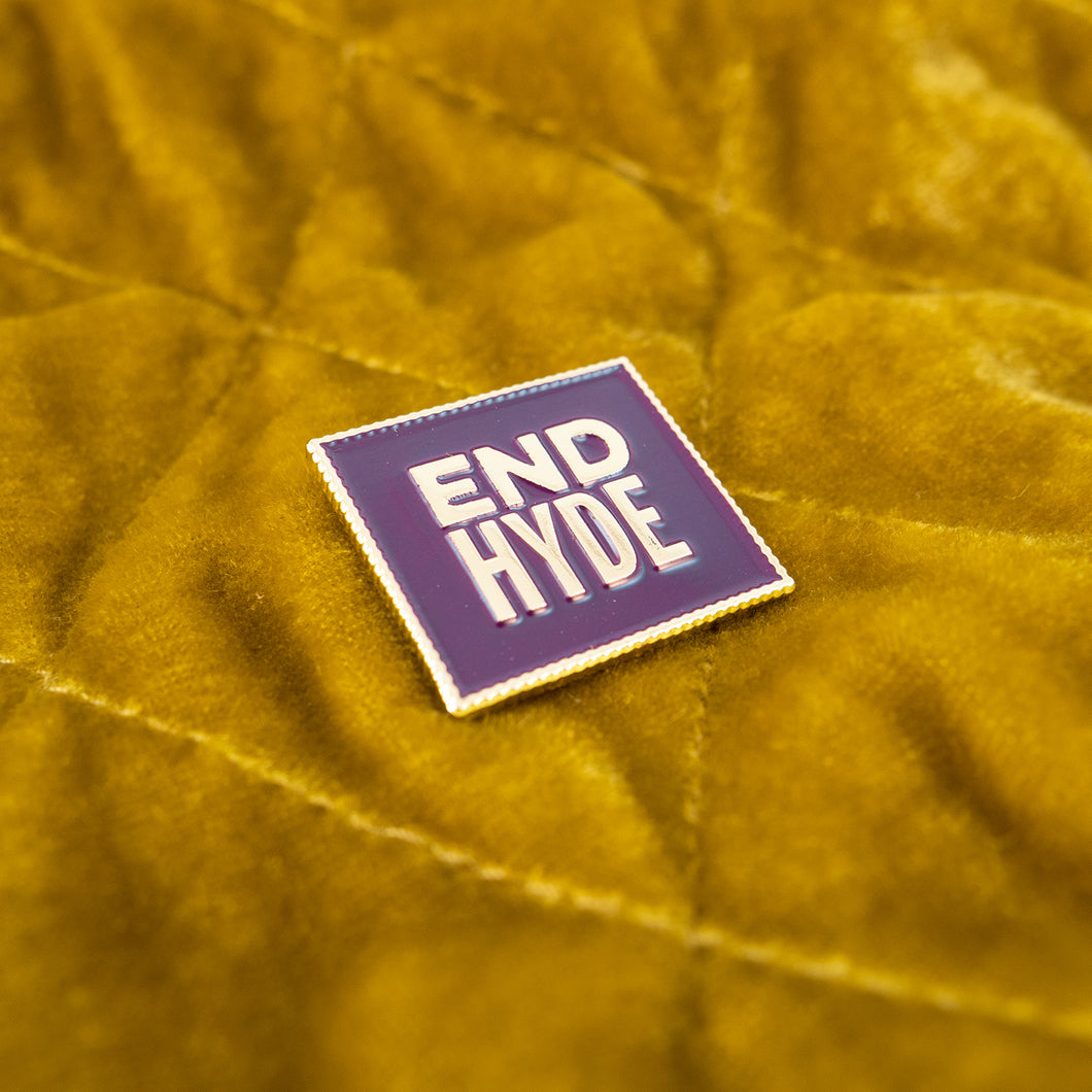 Close-up photo of an enamel lapel pin reading