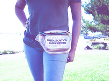 "Load image into Gallery viewer, the midsection of a person wearing jeans and a gold iridescent fanny pack that reads ""Fund Abortions. Build Power."" standing outside in the sun"