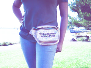 "the midsection of a person wearing jeans and a gold iridescent fanny pack that reads ""Fund Abortions. Build Power."" standing outside in the sun"