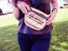"the midsection of a person wearing jeans and holding a gold iridescent fanny pack that reads ""Fund Abortions. Build Power."" standing outside in the sun"
