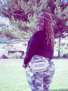 "a young Black woman with long hair wearing a gold iridescent fanny pack that reads ""Fund Abortions. Build Power."" with a black top and camouflage pants"