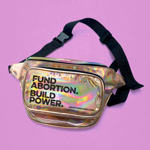 "Photo of a gold holographic vinyl fanny pack with a black nylon strap, imprinted with the text, ""Fund Abortion. Build Power,"" on a light fuchsia background."