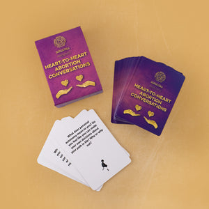 "Photo of a deck of ""Heart-To-Heart Abortion Conversation"" cards, their box, and a few overturned cards, on a yellow background. The top card reads, ""What does personal autonomy mean to you? Do you feel like you can make your own decisions about your path in life? Why or why not?"""