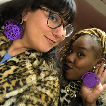 "Photo of two smiling women wearing shiny purple earrings that read ""fund abortion"" on one and ""build power"" on the other."