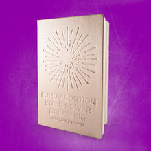 "Load image into Gallery viewer, Photo of a journal with a metallic gold cover, debossed with an illustration of a firework and the text, ""Fund Abortion. Build Power. Dream Big,"" on a purple background."