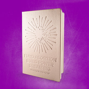 "Photo of a journal with a metallic gold cover, debossed with an illustration of a firework and the text, ""Fund Abortion. Build Power. Dream Big,"" on a purple background."