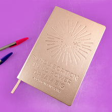 "Load image into Gallery viewer, Photo of a journal with a metallic gold cover, debossed with an illustration of a firework and the text, ""Fund Abortion. Build Power. Dream Big,"" alongside some ballpoint pins, on a lilac-colored background."