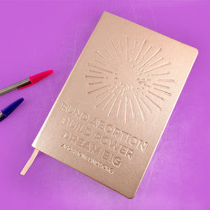 "Photo of a journal with a metallic gold cover, debossed with an illustration of a firework and the text, ""Fund Abortion. Build Power. Dream Big,"" alongside some ballpoint pins, on a lilac-colored background."