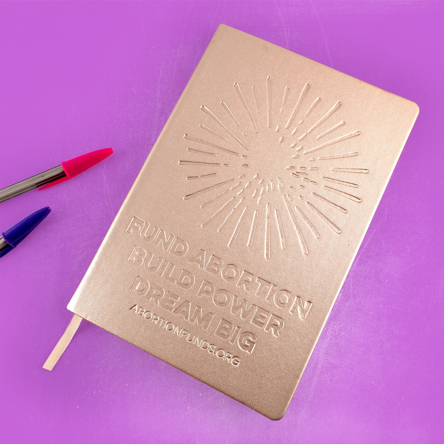 Photo of a journal with a metallic gold cover, debossed with an illustration of a firework and the text,