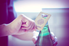 Photo a person using a business-card shaped metal bottle opener. This side of the bottle opener is printed with the National Network of Abortion Funds logo.