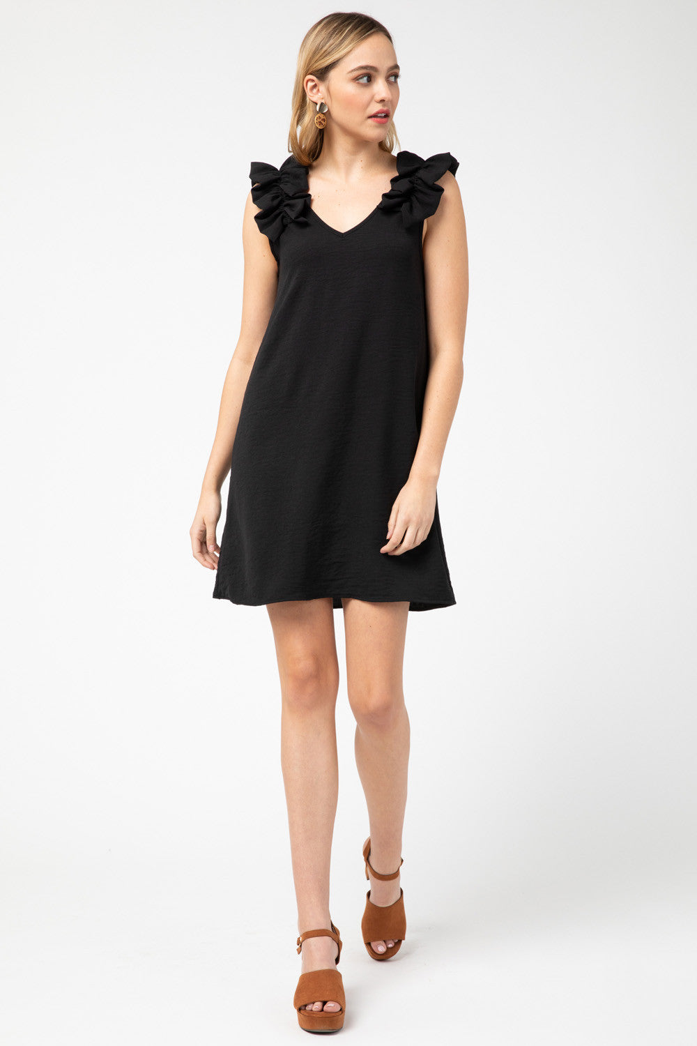 Solid sleeveless v-neck dress featuring ruffle detail at shoulder