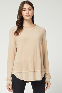 Solid scoop-neck long sleeve top featuring ribbed detail