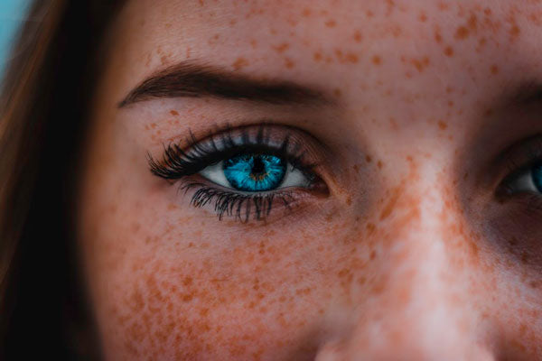 woman with blue eyes and strip eyelash extensions