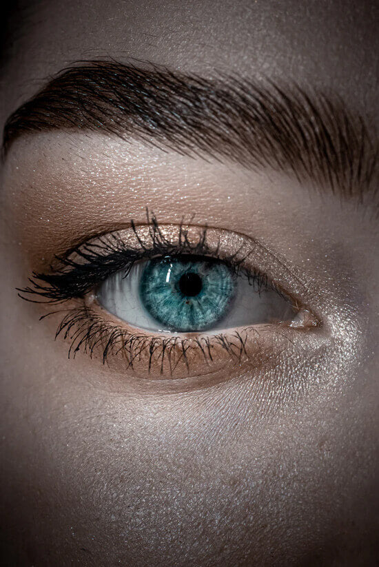 a woman's blue eye with lash extensions and gold eyeshadow