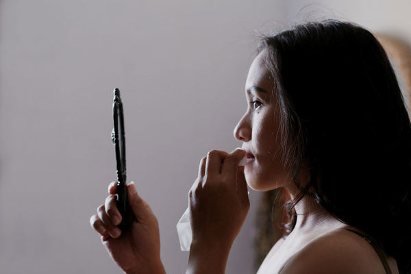 A woman viewing her best lash extensions in a mirror