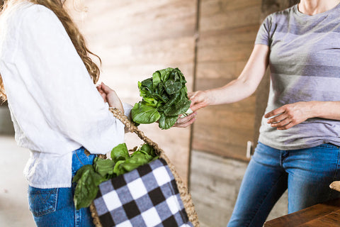 woman handing greens to buyer