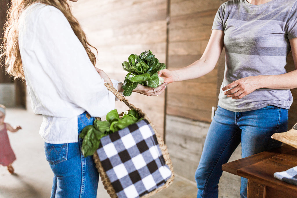 woman buying greens and carrying basket