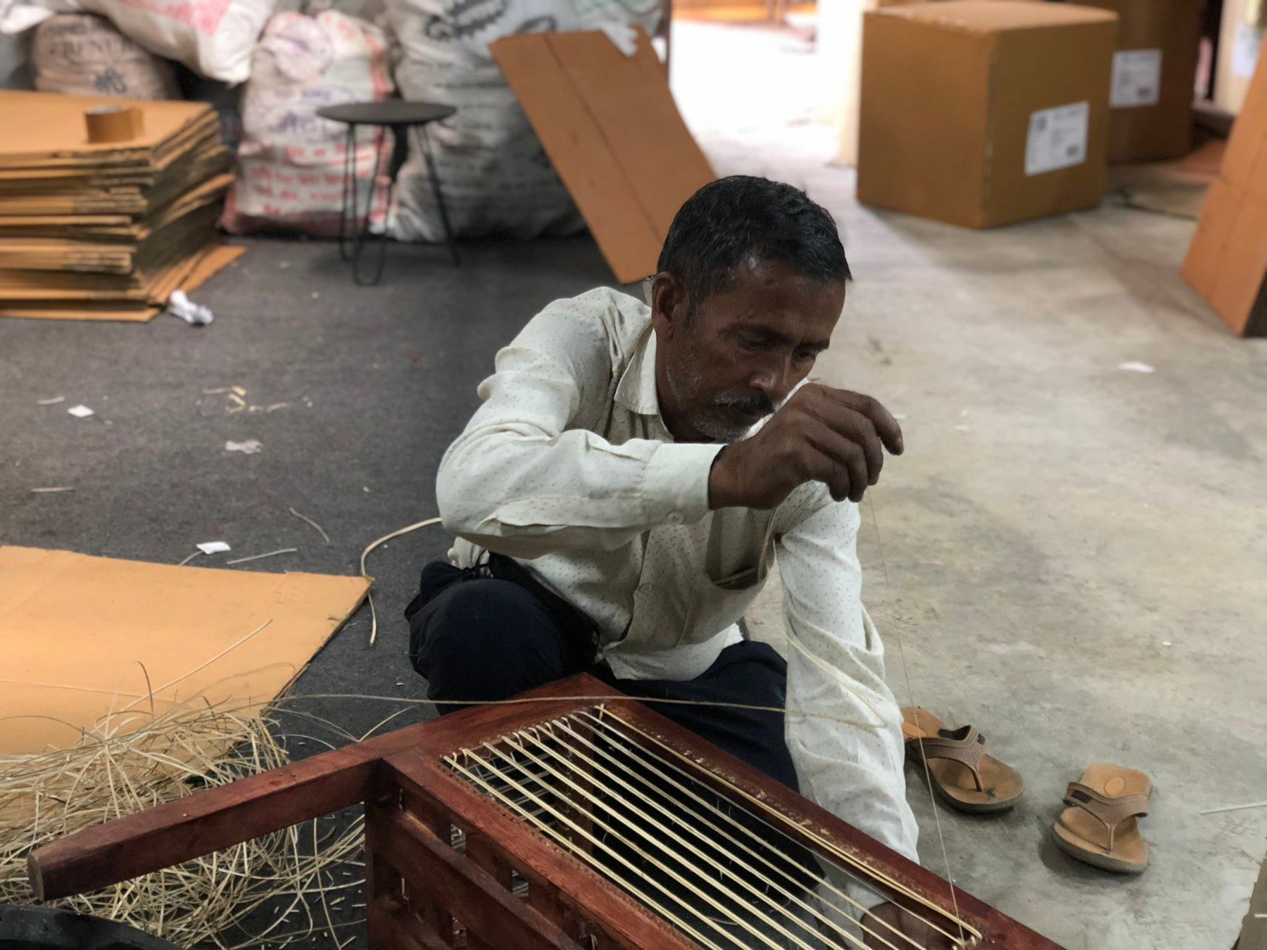 rattan artisan working on our collection of planters